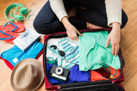 travel bag: summer vacation, travel, tourism and objects concept - close up of woman packing travel bag for vacation