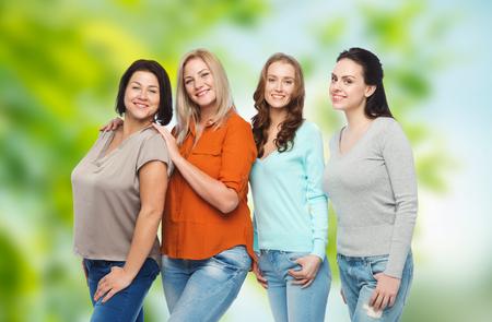 mujeres felices: la amistad, la moda, el cuerpo positivo, diversa y concepto de las personas - grupo de mujeres feliz de tamaño diferentes en ropa casual sobre fondo verde natural
