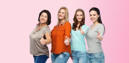 niñas sonriendo: la amistad, la moda, el cuerpo positivo, el gesto y la gente concepto - grupo de diferentes mujeres felices de tamaño en ropa casual que muestra los pulgares para arriba sobre fondo de color rosa Foto de archivo