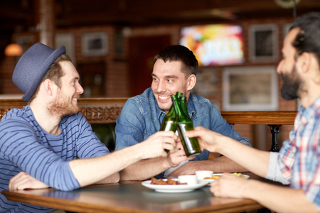 bottled beer: people, leisure, friendship and party concept - happy male friends drinking bottled beer at bar or pub and clinking bottles Stock Photo