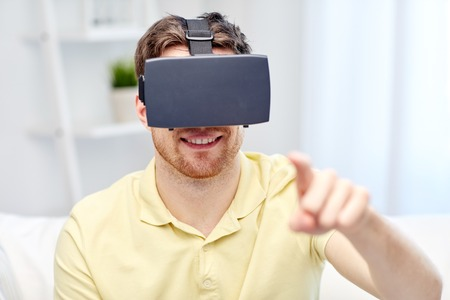 entertainment concept: technology, gaming, entertainment and people concept - happy young man with virtual reality headset or 3d glasses playing video game Stock Photo
