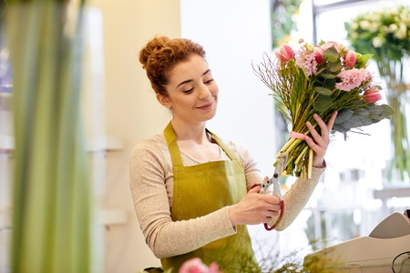 cropping: people, business, sale and floristry concept - happy smiling florist woman making bunch and cropping stems by scissors at flower shop