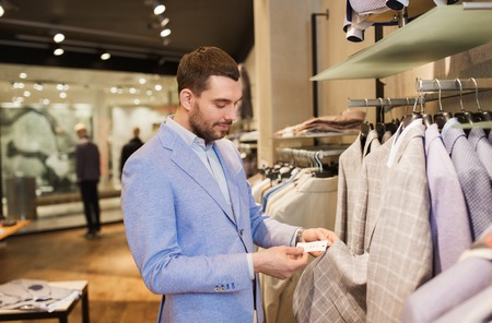 choosing: sale, shopping, fashion, style and people concept - elegant young man in jacket choosing clothes and looking at price tag in mall or clothing store
