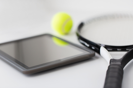 objects equipment: sport, fitness, sports equipment and objects concept - close up of tennis racket with ball and tablet pc computer over white background Stock Photo