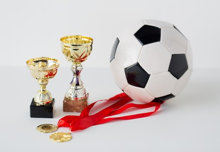 white achievement: sport, achievement, championship, competition and success concept - close up of football or soccer ball with golden medals and cups over white background