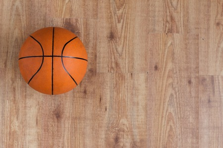 objects equipment: sport, fitness, game, sports equipment and objects concept - close up of basketball ball on wooden floor from top