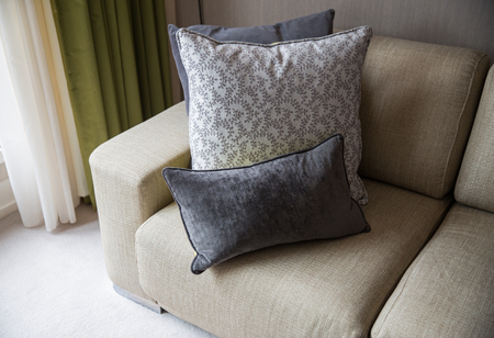comfort room: comfort, furniture and interior concept - close up of couch with cushions at home living room