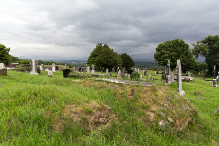 ancient ireland celtic cross: ancient monument and burial concept - old headstones and ruins on celtic cemetery graveyard in ireland