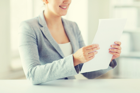 finance report: business, finance and people concept - close up of woman reading papers or tax report at office