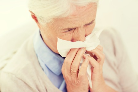 health care, flu, hygiene, age and people concept - sick senior woman blowing nose to paper napkin at home Stock Photo