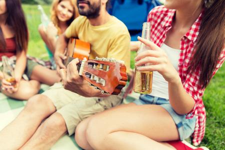 musico: viajes, turismo, ir de excursión, picnic y concepto de las personas - grupo de amigos felices con tienda de campaña y bebidas que toca la guitarra en el camping