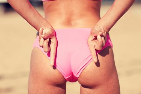 fila de personas: verano, el deporte, el gesto, las vacaciones y la gente concepto - cerca de las nalgas y las manos de la mujer que muestra signo de la mano de voleibol de playa que significa bloque de línea de ataque Foto de archivo