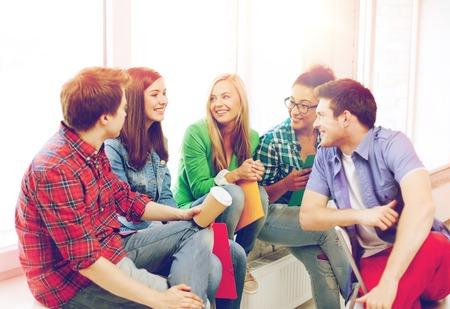 jovenes estudiantes: concepto de la educación - los estudiantes comunicarse y riendo en la escuela Foto de archivo