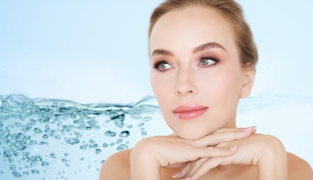 blue face: beauty, people, moisturizing and skincare concept - beautiful young woman face and hands over white background