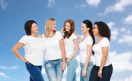 mujeres juntas: amistad, diversa, corporal positiva y la gente concepto - grupo de mujeres felices diferentes tamaños en las camisetas blancas abrazando sobre el cielo azul y las nubes de fondo Foto de archivo