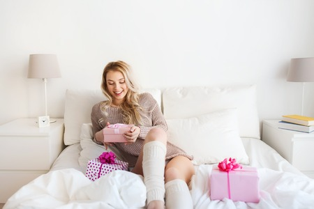 legwarmers: holidays, birthday, christmas morning and people concept - happy young woman gift boxes or presents in bed at home bedroom Stock Photo