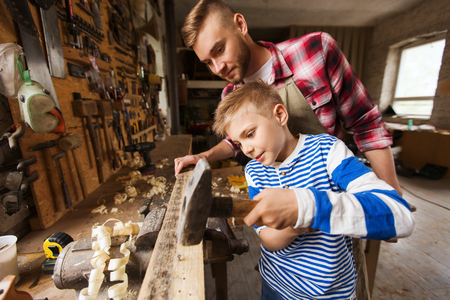 hammering: happy family, carpentry, woodwork and people concept - father and little son with hammer hammering nail into wood plank at workshop
