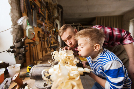 vise: family, carpentry, woodwork and people concept - father and little son blowing shavings off wood plank at workshop