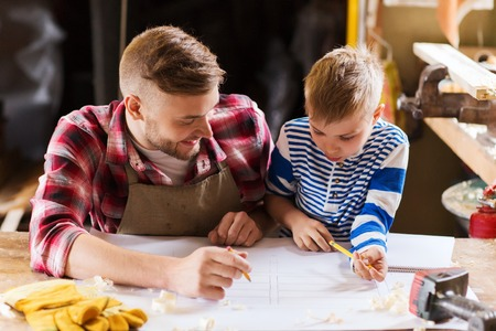 family, carpentry, woodwork and people concept - happy father and little son with blueprint at workshop Stock Photo