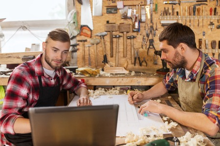 chippy: profession, carpentry, technology and people concept - two carpenters with laptop computer and blueprint at workshop