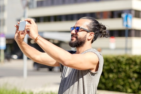 taking video: travel, tourism, technology and people concept - smiling man taking video or selfie by smartphone on summer city street