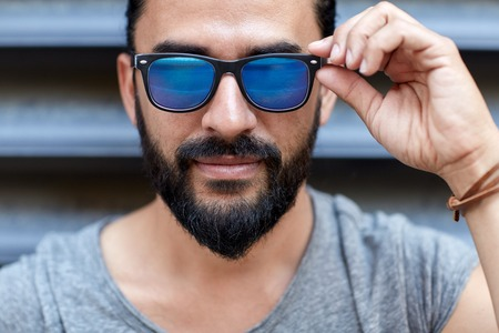 middle eastern: lifestyle, emotion, expression and people concept - happy smiling man with sunglasses and beard on city street