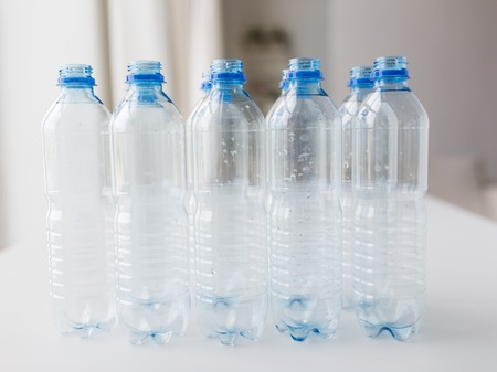 water bottles: recycling, healthy eating and food storage concept - close up of clean empty used plastic water bottles on table
