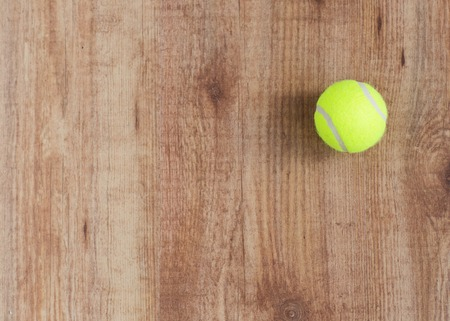 objects equipment: sport, fitness, game, sports equipment and objects concept - close up of tennis ball on wooden floor from top