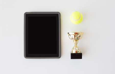 white achievement: sport, achievement, championship and technology concept - close up of tennis ball, golden cup and tablet pc computer with black blank screen over white background from top