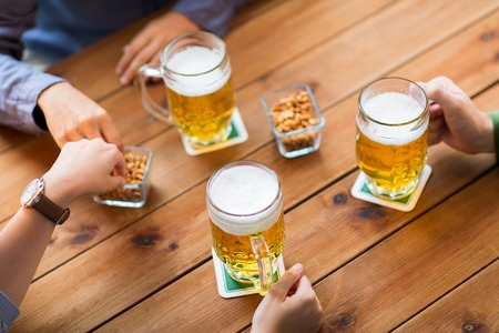 man nuts: people, leisure and drinks concept - close up of male hands with beer mugs and peanuts at bar or pub