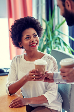 african business man: business, startup, people and drinks concept - happy african woman taking coffee cup from man in office Stock Photo