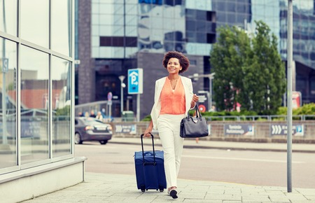 black professional: travel, business trip, people and tourism concept - happy young african american woman with travel bag walking down city street Stock Photo