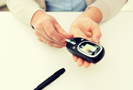 blood sugar level: medicine, age, diabetes, health care and people concept - close up of senior woman with glucometer and test stripe checking blood sugar level at home