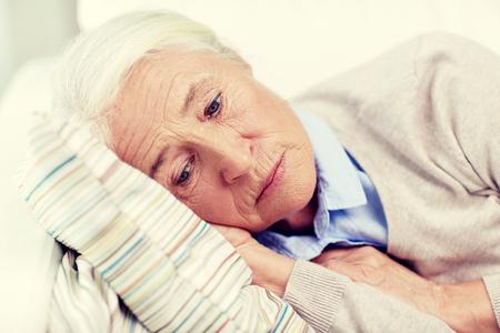 gente durmiendo: age, sadness, trouble, problem and people concept - sad senior woman sleeping on pillow at home Foto de archivo