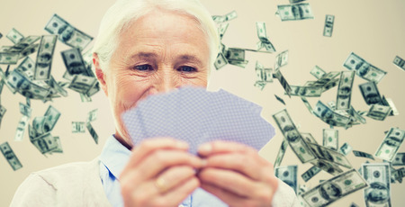 age, game, gamble, poker and people concept - close up of happy smiling senior woman playing cards over dollar money rain on background Stock Photo