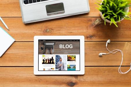 미디어, 인터넷, 비즈니스 및 기술 개념 - 태블릿 pc 컴퓨터 화면, 노트북 및 나무 테이블에 이어폰에 블로그 웹 페이지의 가까이