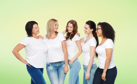 multiracial: friendship, diverse, body positive and people concept - group of happy different size women in white t-shirts hugging over green natural background Stock Photo