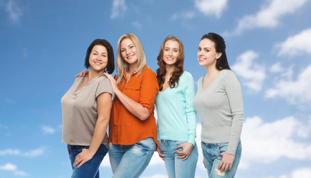 middle age women: friendship, fashion, body positive, diverse and people concept - group of happy different size women in casual clothes over blue sky and clouds background