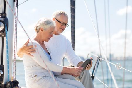 항해, 기술, 관광, 여행 및 사람들이 개념 - 해피 보트 또는 바다에 떠있는 요트 갑판에 태블릿 pc 컴퓨터와 함께 행복 한 고위 커플