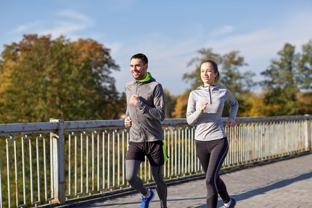 tracksuit: fitness, sport, people and lifestyle concept - happy couple running outdoors