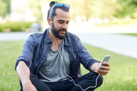 people, music, technology, leisure and lifestyle - happy young hipster man with earphones and smartphone sitting on grass