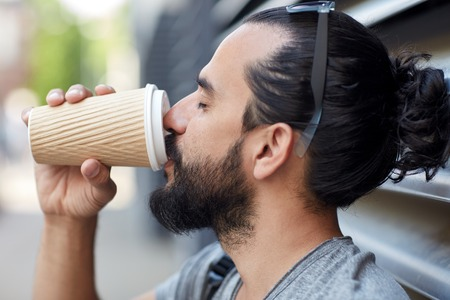 hombre tomando cafe: people, drinks, leisure and lifestyle - man drinking coffee from disposable paper cup on city street Foto de archivo