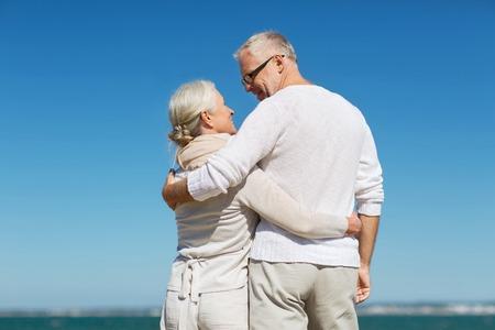 mujeres de espalda: familiar, la edad, los viajes, el turismo y el concepto de la gente - feliz pareja de alto nivel que abrazan en la playa del verano Foto de archivo