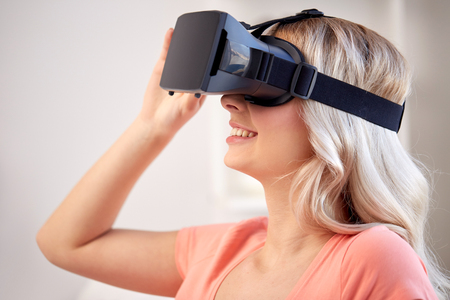 virtual technology: technology, virtual reality, cyberspace, entertainment and people concept - happy young woman with virtual reality headset or 3d glasses at home Stock Photo