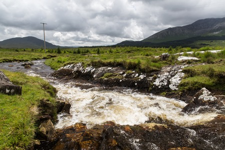 terrain: nature and landscape concept - view to river rapids and hills or mountains at connemara in ireland