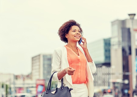 happy worker: business, communication, technology and people concept - young smiling african american businesswoman calling on smartphone in city