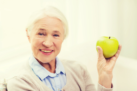 persona de la tercera edad: age, healthy eating, food, diet and people concept - happy smiling senior woman with green apple at home