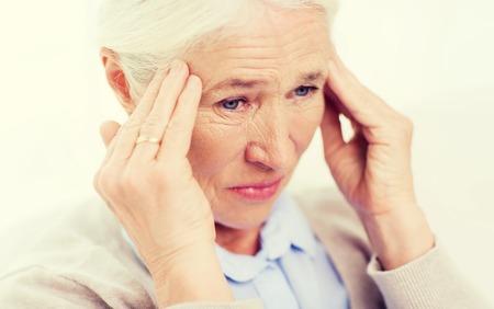 agotado: cuidado de la salud, el dolor, el estrés, la edad y el concepto de la gente - la cara de la mujer mayor que sufre de dolor de cabeza