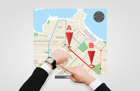 gprs: business, people and modern technology concept - close up of businessman pointing to smart watch at his hand with gps navigator map on screen Stock Photo