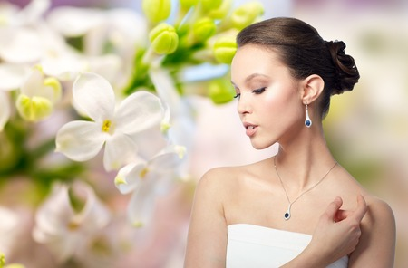 jewelry background: beauty, jewelry, wedding accessories, people and luxury concept - beautiful asian woman or bride with earring and pendant over natural spring lilac blossom background